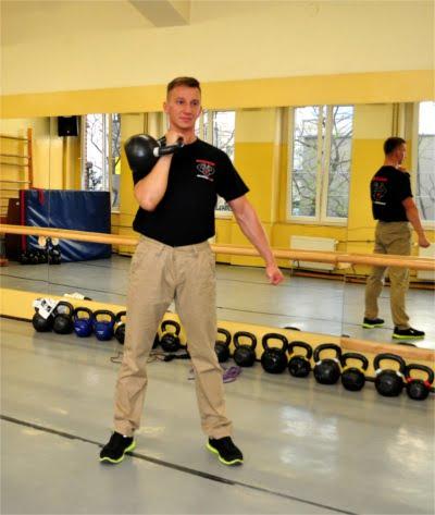 Military press - krok pierwszy, zepnij ciało, wyjdź z Rack Position.