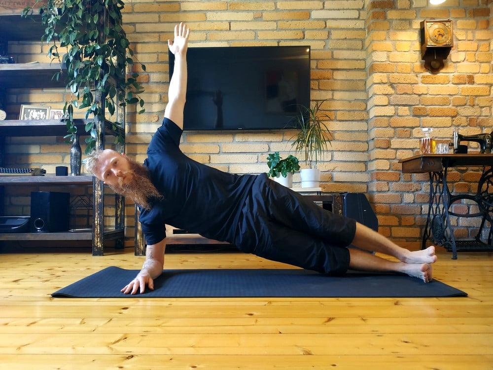 Plank bokiem na przedramieniu z drugą ręką w górze.