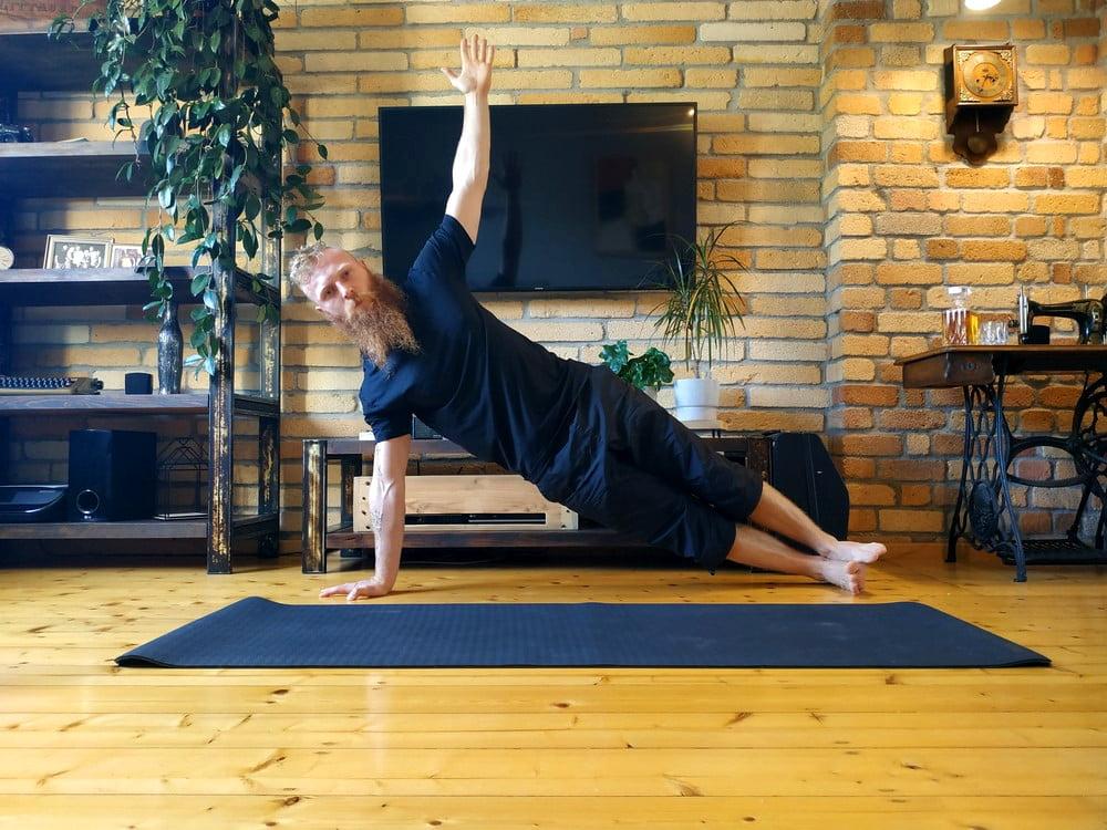 Ćwiczenie deska bokiem na ręce wyprostowanej z druga ręką wyprostowaną w górę.