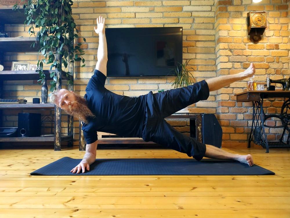 Plank boczny z podniesioną ręką i nogą w podparciu na łokciu.
