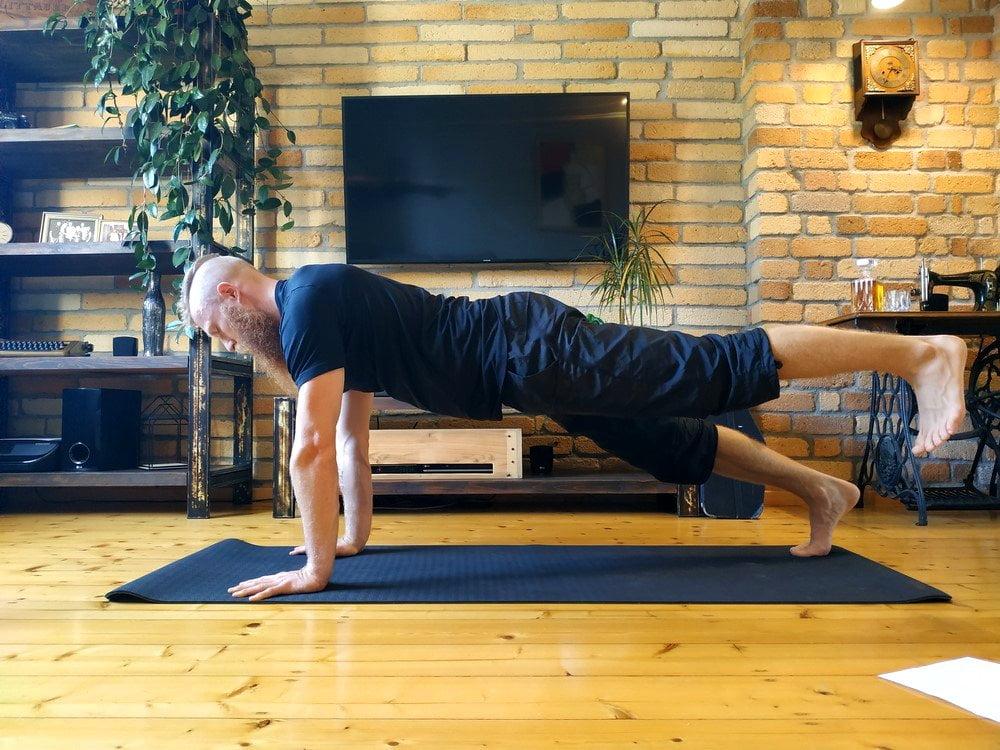Plank na wyprostowanych rękach z podniesioną nogą.
